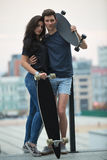 Pair of lovers teen is posing for the camera. In an embrace with two longboard. Against the background of the urban landscape Stock Photos