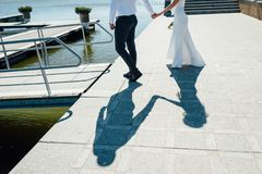 A pair of lovers walk on the pier near the yachts stock photo