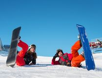 Pair lying with their snowboards on ski slope and looking at the camera with smile. On the background of blue sky on a sunny winter day stock image