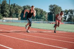 A pair of male athletes compete in running. A pair of male athletes compete in a race at the stadium Royalty Free Stock Photography