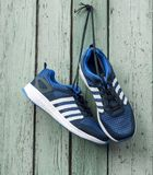 Pair of male blue textile sneakers suspended on laces. On a old wooden wall royalty free stock photo