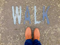 Pair of Male brown shoes point towards the word WALK. Pair of male feet in brown shoes and trousers point toe up at the word WALK stencilled in blue letters on Royalty Free Stock Image