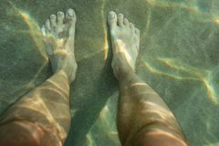 Pair of male feet on sun lit sand sea bottom, view from above, u royalty free stock images