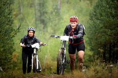Pair of male and female mountainbikers climb a step uphill in forest. Revda, Russia - July 31, 2016: pair of male and female mountainbikers climb a step uphill Royalty Free Stock Images