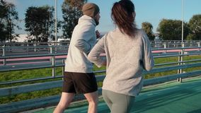 Couple of young sportspersons are running on track of olympic stadium. Pair of male and female runners is training outdoors. They are moving on path of modern stock footage