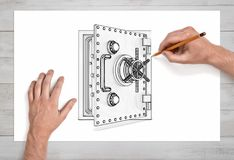 A pair of male hands in close view draws an open metal safe box with a pencil on white paper. Royalty Free Stock Image