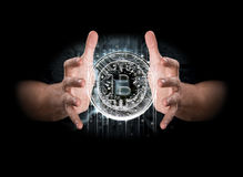 A pair of male hands enveloping a hologram of a bitcoin Stock Image