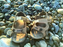 A pair of male leather sandals on the stone beach under sunlight. Near the sea Stock Images