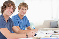 A pair of male students smiling. As they both look at the camera Royalty Free Stock Images