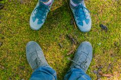 Pair of Man and woman feet in love Romantic Outdoor with moss on the background life-Style Fashion concept. Tourists Stock Photos