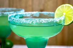 Pair of margaritas. In festive blue and green glasses against a wooden background Royalty Free Stock Photography