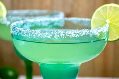 Pair of margaritas. In festive blue and green glasses against a wooden background Royalty Free Stock Image