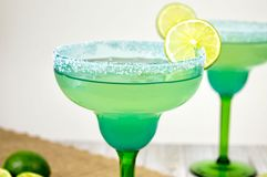 Pair of margaritas. In festive blue and green glasses against a wooden background Royalty Free Stock Photos