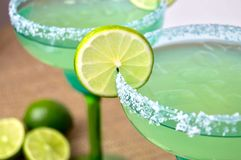 Pair of margaritas with salted rims. Pair of salted margaritas with lime in festive blue and green glasses Royalty Free Stock Images