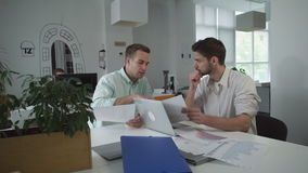 Pair of marketer looking on graphs and charts discussing results of sales. stock footage