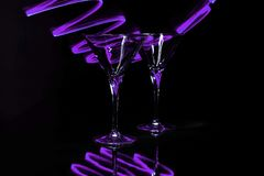 Pair martini glasses with purple light trails Royalty Free Stock Image