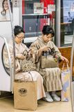 Pair of mature ladies in traditional Japanese clothes sitting in the Tokyo subway, Japan stock photos