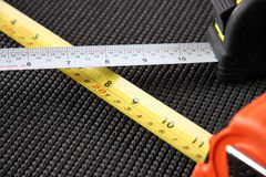 Pair Of Measuring Tapes. Two measuring tapes on a black textured surface Royalty Free Stock Photos