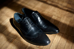 Pair of men's black leather ankle shoes placed on wooden floor Royalty Free Stock Images