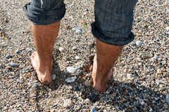 Pair of men's feet. On the beach with pebbles Royalty Free Stock Images