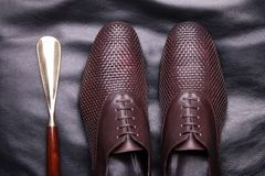 A pair of men shoes with laces. Men classic shoes. Luxury shoes from woven leather and a spoon for shoes stock photography