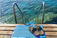 Beach Shoes. A pair of mens leather sandals by steps leading to sea stock images