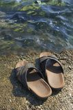 Beach Shoes. A pair of mens leather sandals on water's edge by sea stock photography