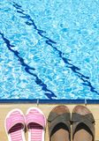 Beach Shoes. A pair of mens and womans sandals by side of swimming pool stock photos