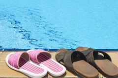 Beach Shoes. A pair of mens and womans sandals by side of swimming pool royalty free stock images