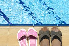Beach Shoes. A pair of mens and womans sandals by side of swimming pool royalty free stock photos