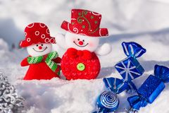 A pair of merry snowmen in the snow with Christmas toys with blue candies and a silvery snowflake. Merry Christmas Stock Photography