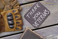 Pair of military veteran`s gloves and old book. Top view, flat lay. Thank you veterans concept Stock Photography