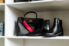 Pair of black leather shoes with low heels and a black bag with a gold buckle and a red belt on a white shelf in the store stock photo