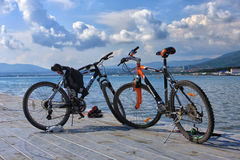 Pair of mountain bikes standing on the Black sea pier on scenic seaside background Stock Image
