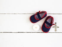 Pair of navy and red baby booties, candle and cross on white woo Royalty Free Stock Photography