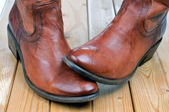 Pair of classic leather brown cowboy boots. Pair of new classic leather brown cowboy boots on wooden boards. Macro shooting royalty free stock photos