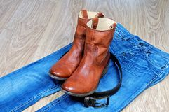 Leather brown cowboy boots and belt on blue jeans stock photography