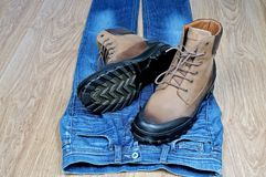 Men`s leather boots on blue jeans royalty free stock images