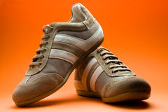 Casual Brown Shoes. A pair of new male casual brown shoes on orange background Stock Photography