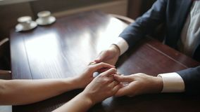 A pair of newlyweds holding hands in a cafe. Close up of human hands. stock video footage