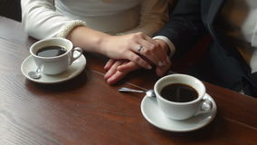 A pair of newlyweds holding hands in a cafe. Close up stock video footage