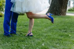 A pair of newlyweds hugs a luscious. Green grass on a sunny day. He has bright blue trousers, a bright blue tuflin high heel. The girl lifted her foot in the stock photo