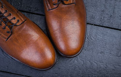 A pair of nice brown leather shoes. Brown leather shoes on a black wooden floor Royalty Free Stock Image