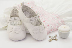 Pair Of White Baby Shoes On Embroidered Christening White Dress, Cross And Candle Royalty Free Stock Image