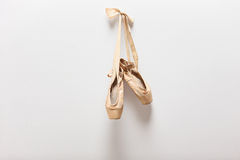 Pair of old ballet shoes hanging on a wall Royalty Free Stock Photo