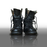 Pair of old black combat. On reflect floor Royalty Free Stock Photo