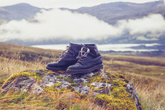 Pair of old  black walking boots on a rock in the mountains Stock Photo