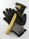 Pair of old black work gloves and a hammer Stock Image