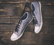 Pair of old blue male shoes hanging on a nail Royalty Free Stock Images