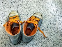 A pair of old blue and orange sneaker. On the marble floor. The shoe had some dirt inside Royalty Free Stock Photo